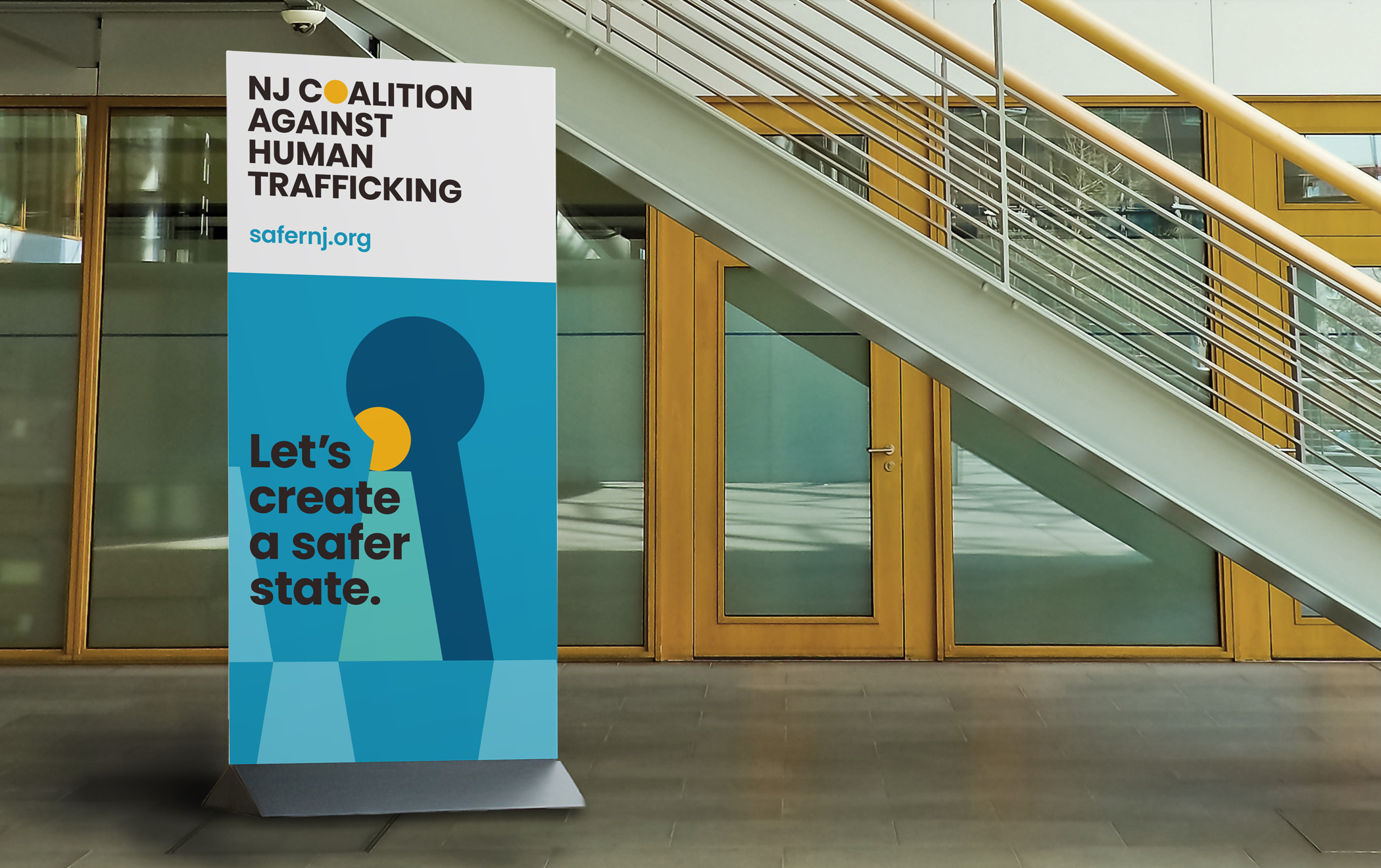 """Pull-up banner with NJ Coalition Against Human Trafficking branding reads """"Let's create a safer state. safernj.org"""""""