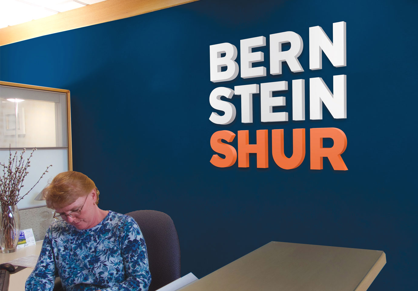 The Bernstein Shur logo on a dark blue wall in the company reception area. A person sits a the desk in the foreground.