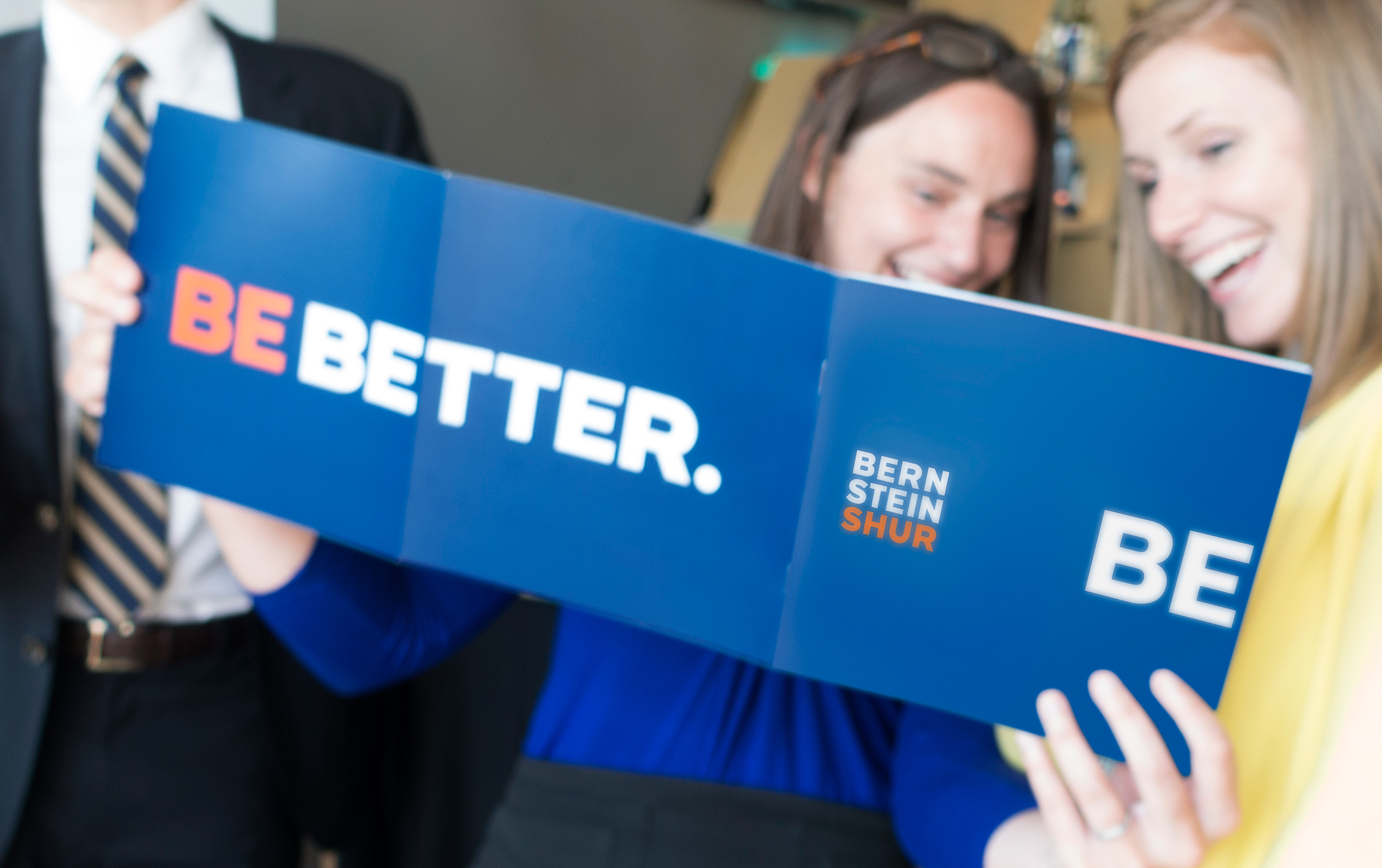 """Two employees holding and looking at an opened Bernstein Shur brand spirit booklet with the title """"Be better."""""""