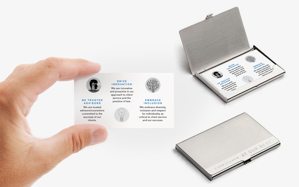 """A hand holding an illustrated Cadwaleder """"At our best"""" promotional card with two sets of the cards in cases in the background"""