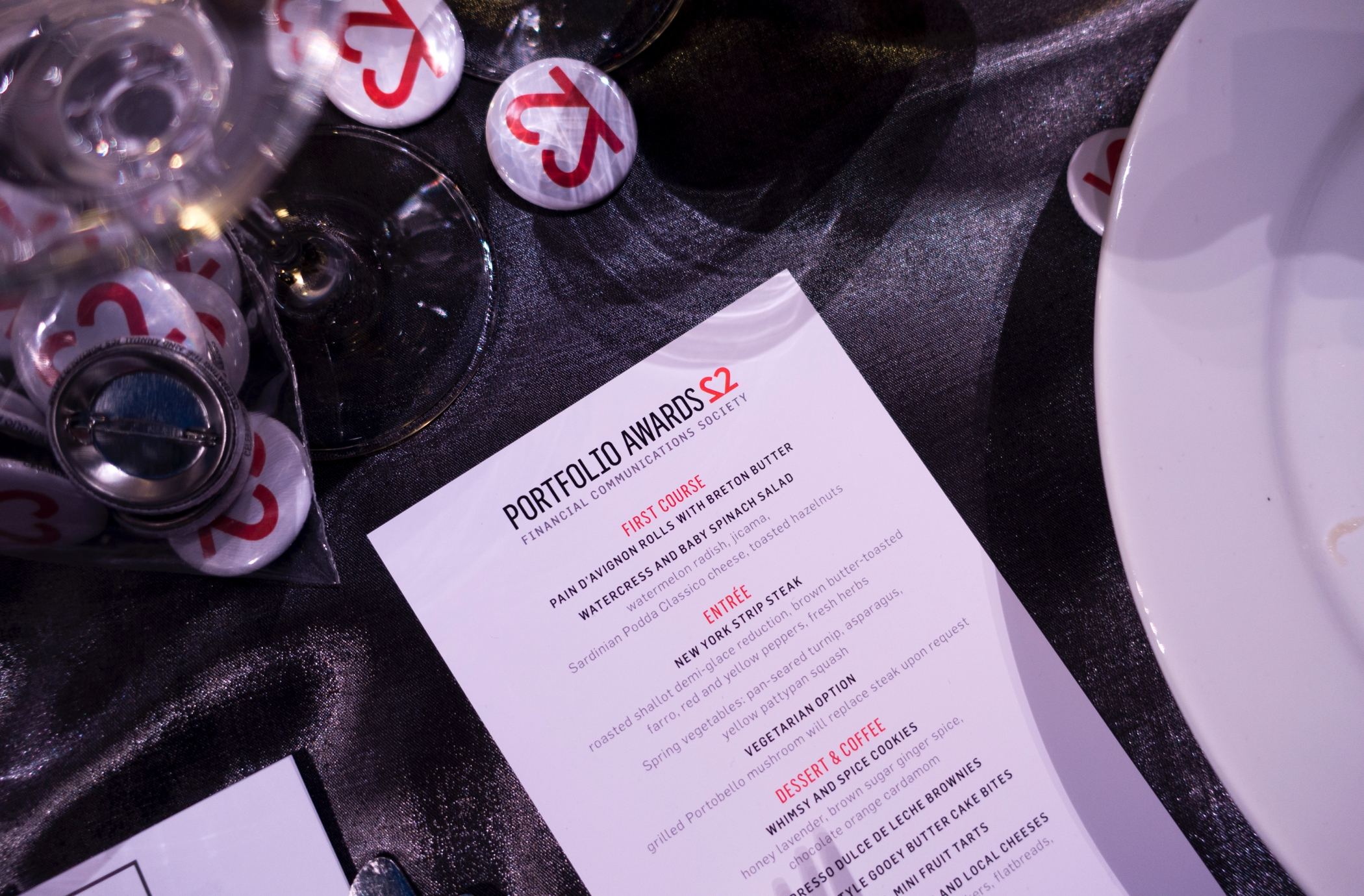 Financial Communications Society 22nd Portfolio Awards menu card on a table with several event logo buttons.