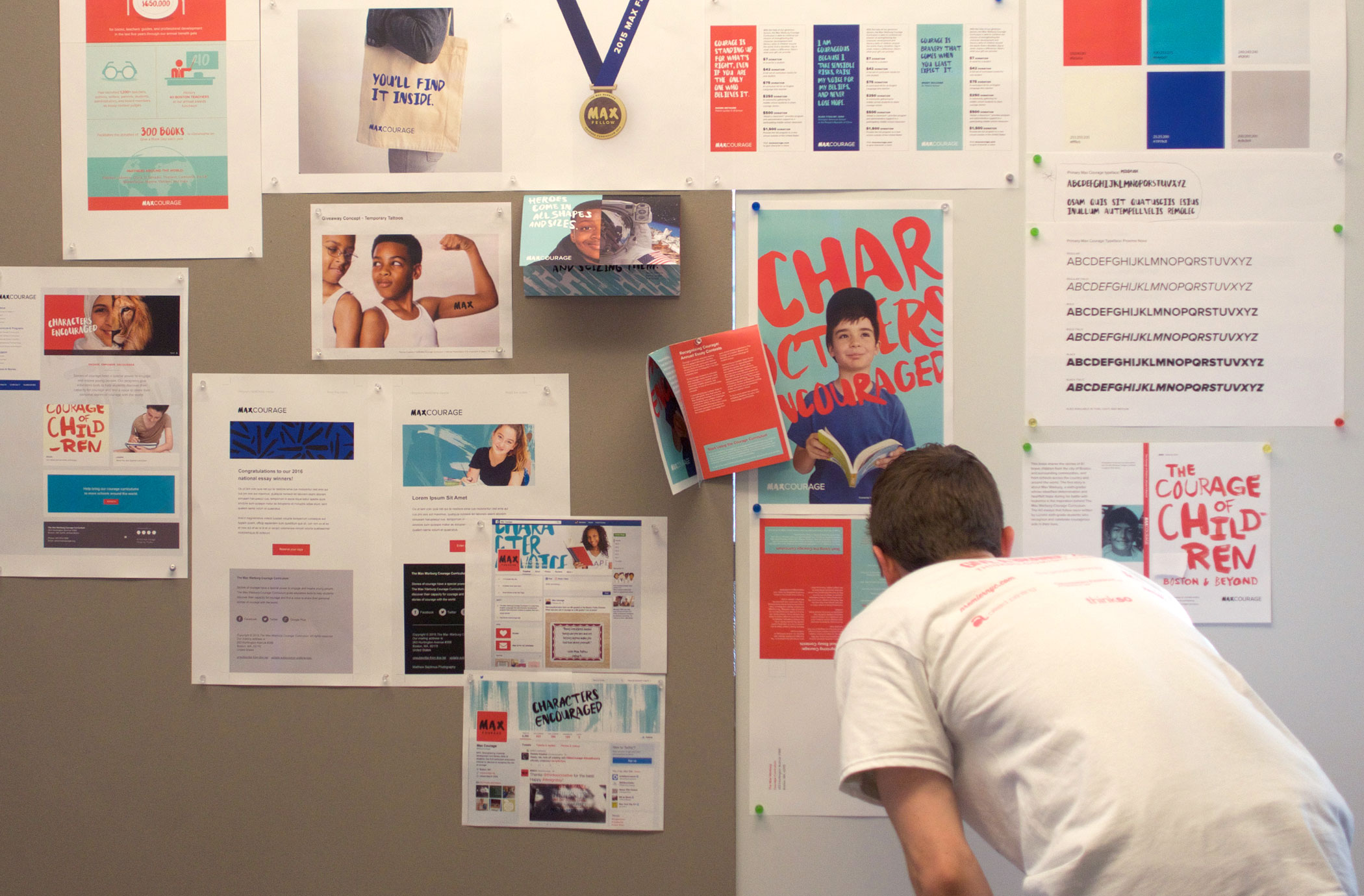 A person leans into to look at designs tacked to the wall for the 2015 Give A Brand design sprint.