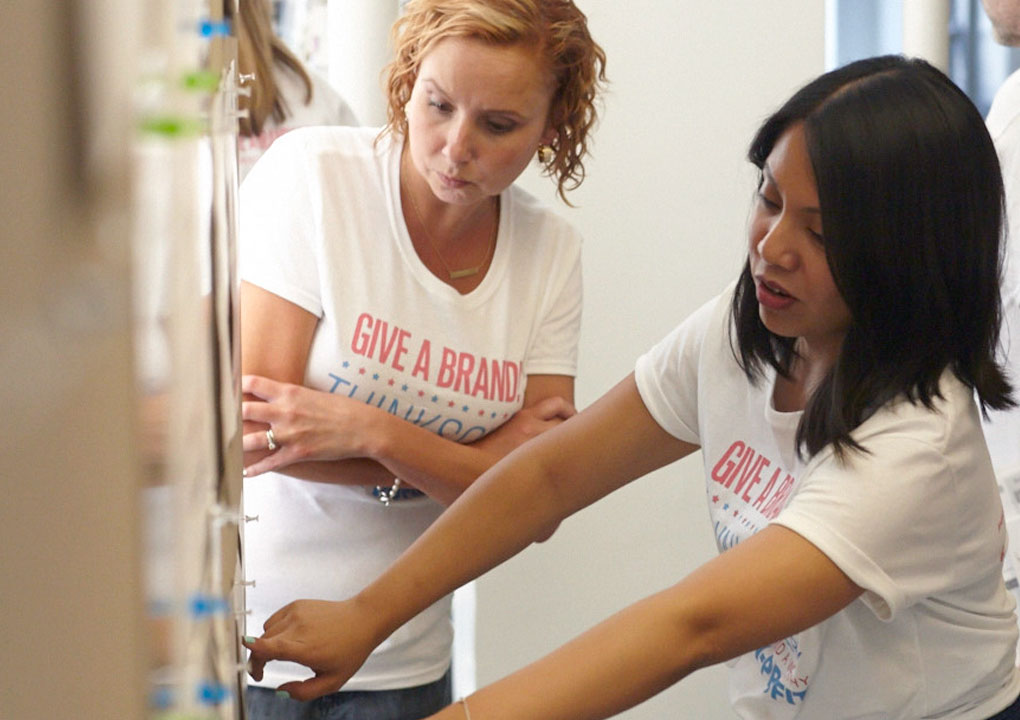 Two Give A Brand team members discuss material on the design wall during the Give A Brand design sprint.
