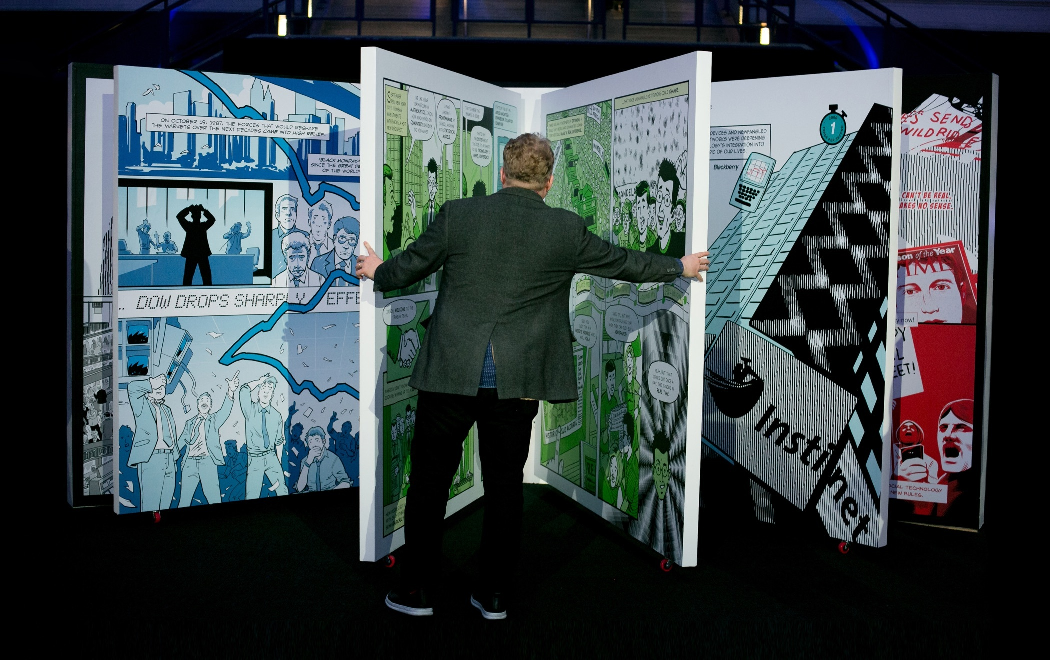 A rear view of a person opening the pages of a 7 foot tall version of Instinet's Fintech at Fifty graphic novel.