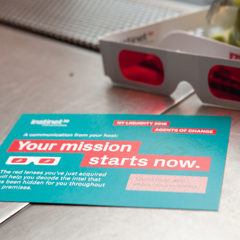 An invitation to an Instinet client event on a tabletop next to a pair of red and blue 3D classes  with the headline Your mission starts now.