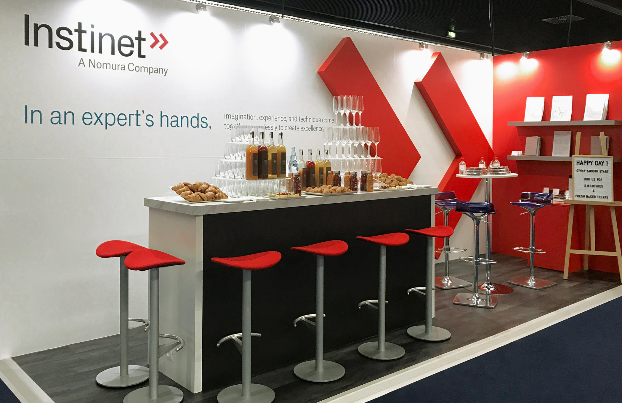 The Instinet reception booth at an industry conference with seating area in front of a giant, wall-mounted sculpture of the red, dual chevron brand emblem.