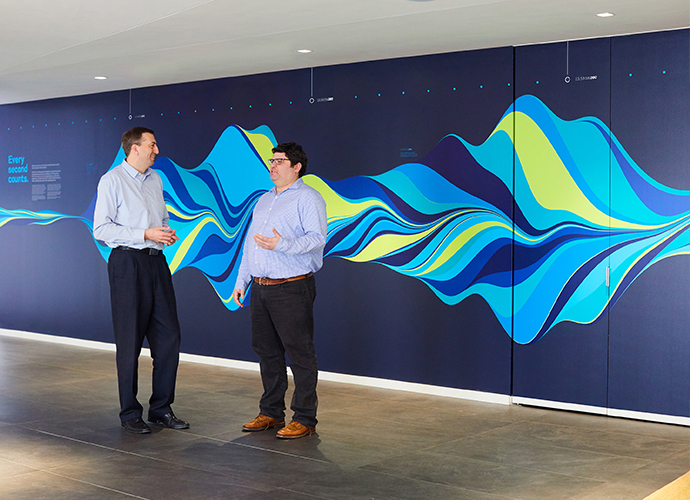 Two KCG employees stand in front of a multi-colored wave pattern mural that depicts one second of market trading activity.