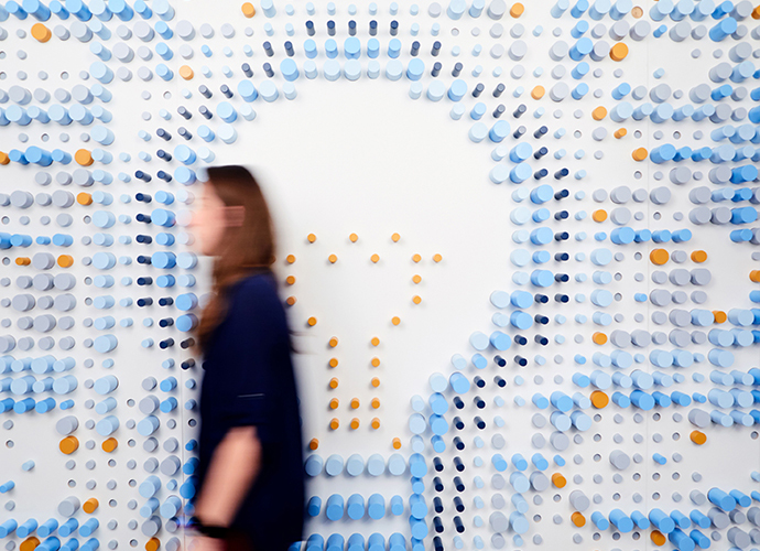 A figure walks in front of a  wall sculpture in the KCG office: the image of a light bulb formed from colored wooden dowels.