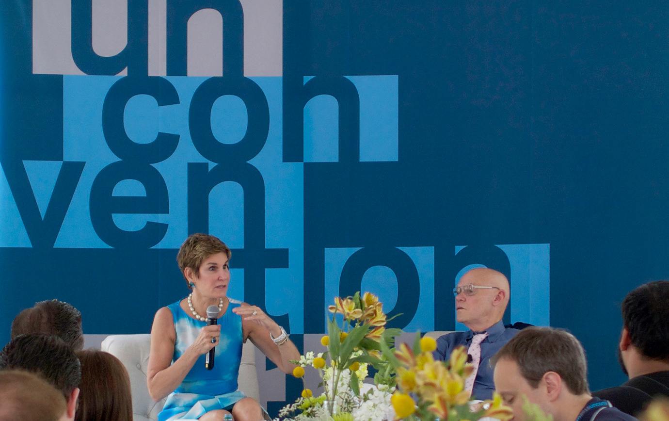 A seated presenter speaks to a group of attendees in front of a wall painted with a large KCG Un-convention event logo.