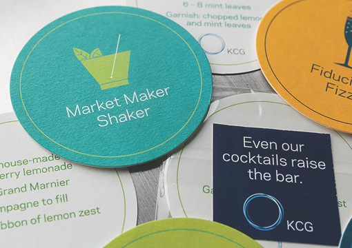 """Custom drink coasters from the 2014 KCG Uncon client event with the slogans 'Market Maker Shaker,"""" and """"Fiduciary Fizz."""""""