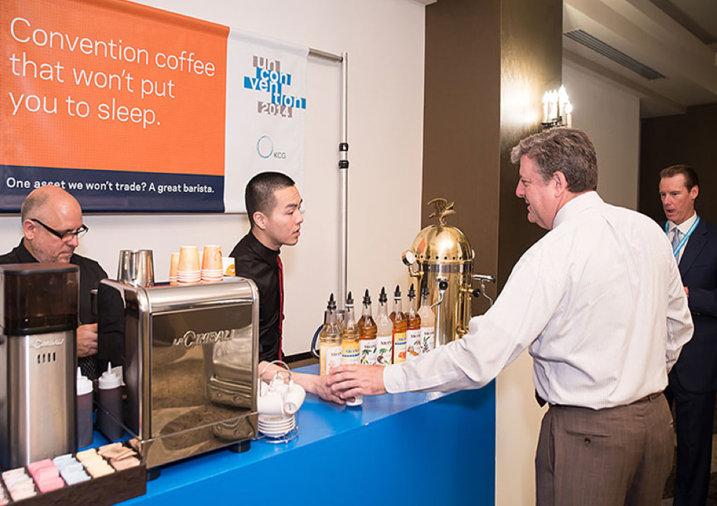 A 2014 KCG Uncon client event attendee grabs a coffee from the refreshment station during a conference break.