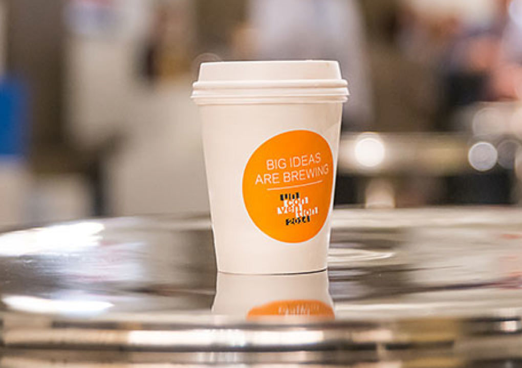 """Close up of a 2014 KCG Uncon client event branded coffee cup with the slogan """"Big ideas are brewing."""""""