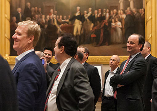 A group of 2014 KCG Uncon client event attendees in front of a painting of the signing of the Declaration of Independence.