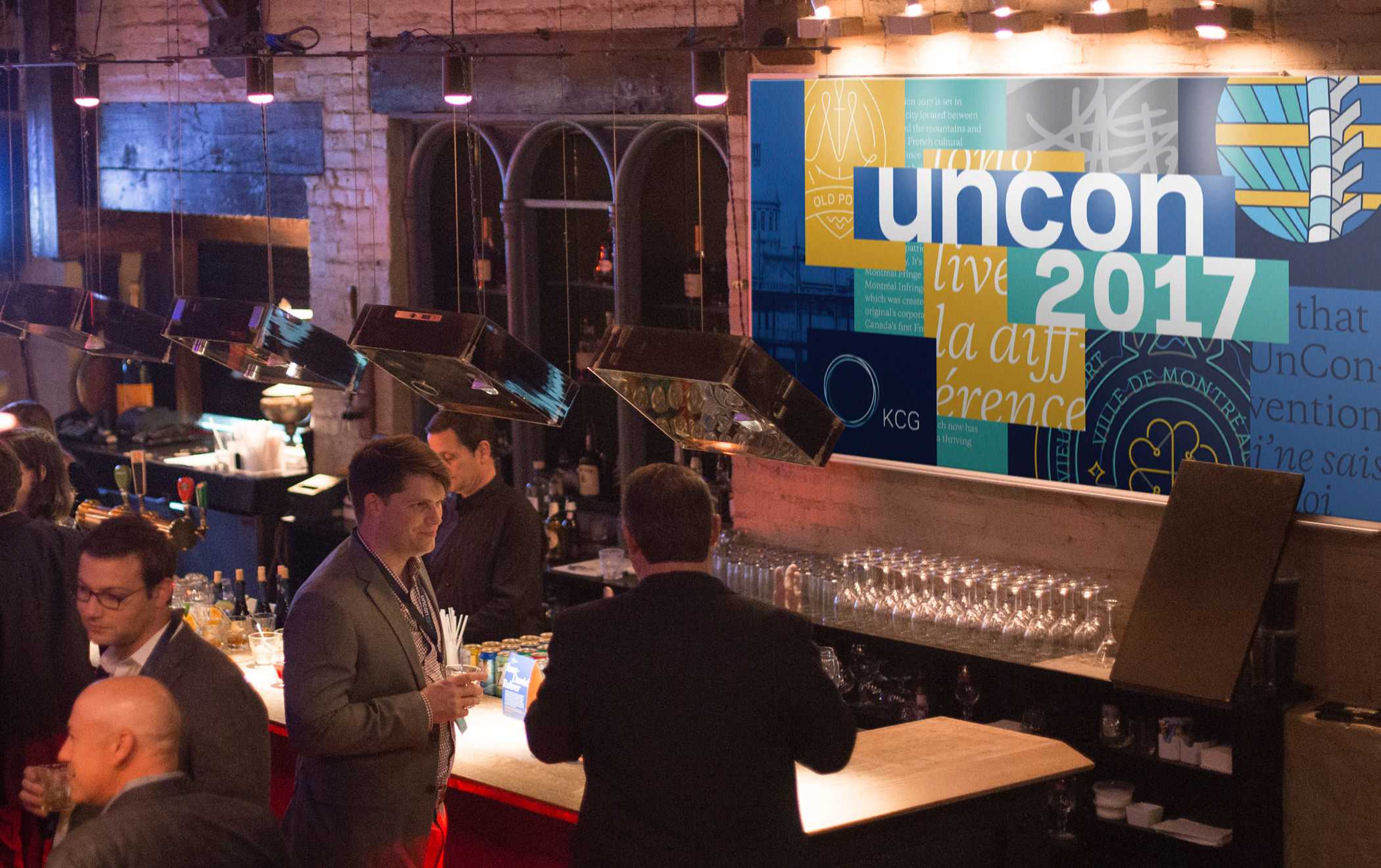 Attendees enjoying drinks near the bar during a cocktail reception at the 2017 KCG Uncon client event.