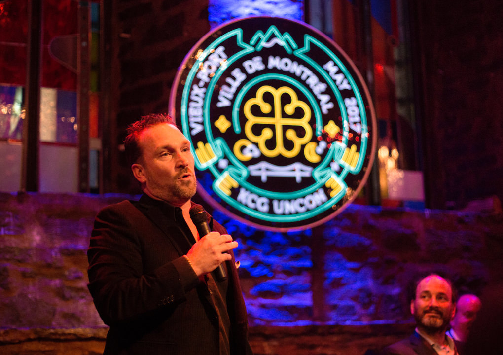 A speaker addresses attendees during an evening reception in front the neon sign logo for 2017 KCG Uncon client event.