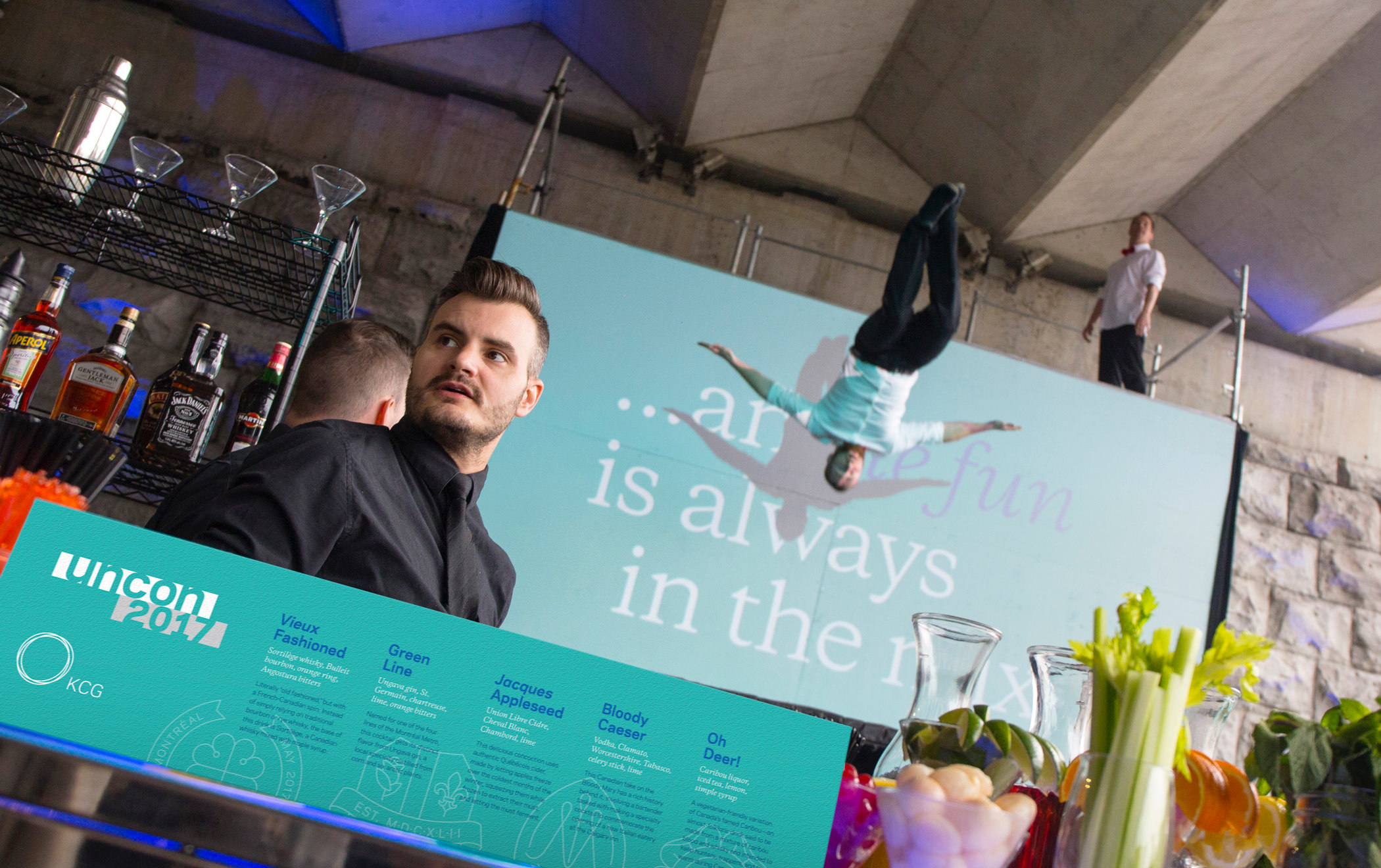 A bartender and cocktail menu sign at the 2017 KCG Uncon client event. A pair of acrobats perform in the background.