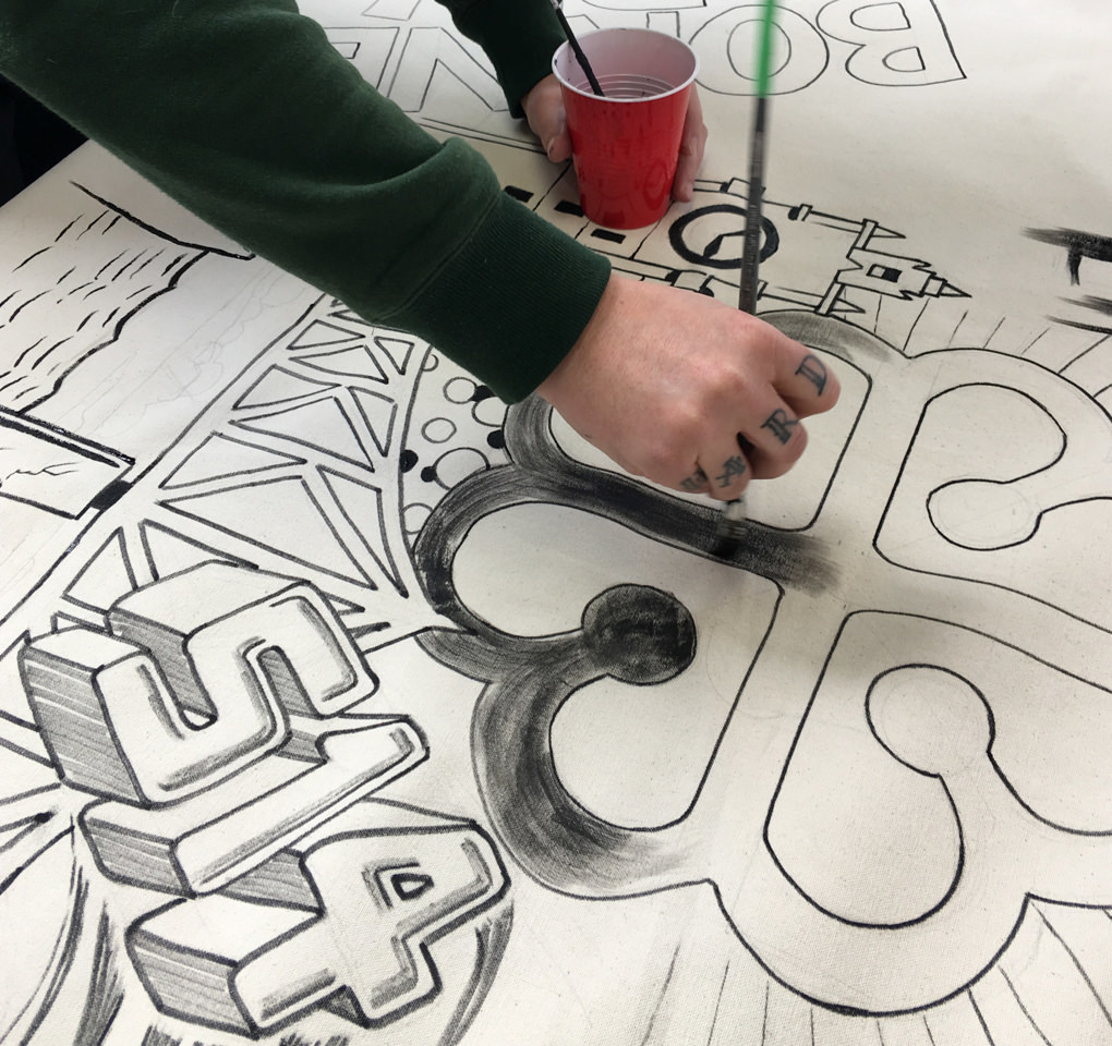An artist painting and lettering a piece of white canvas to be cut and made into tote bags for the 2017 KCG Uncon event.