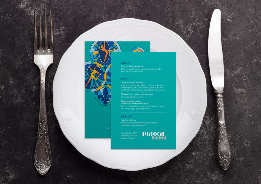 A place setting with a knife, fork, plate, and illustrated menu cards for a dinner at the 2017 KCG Uncon client event.