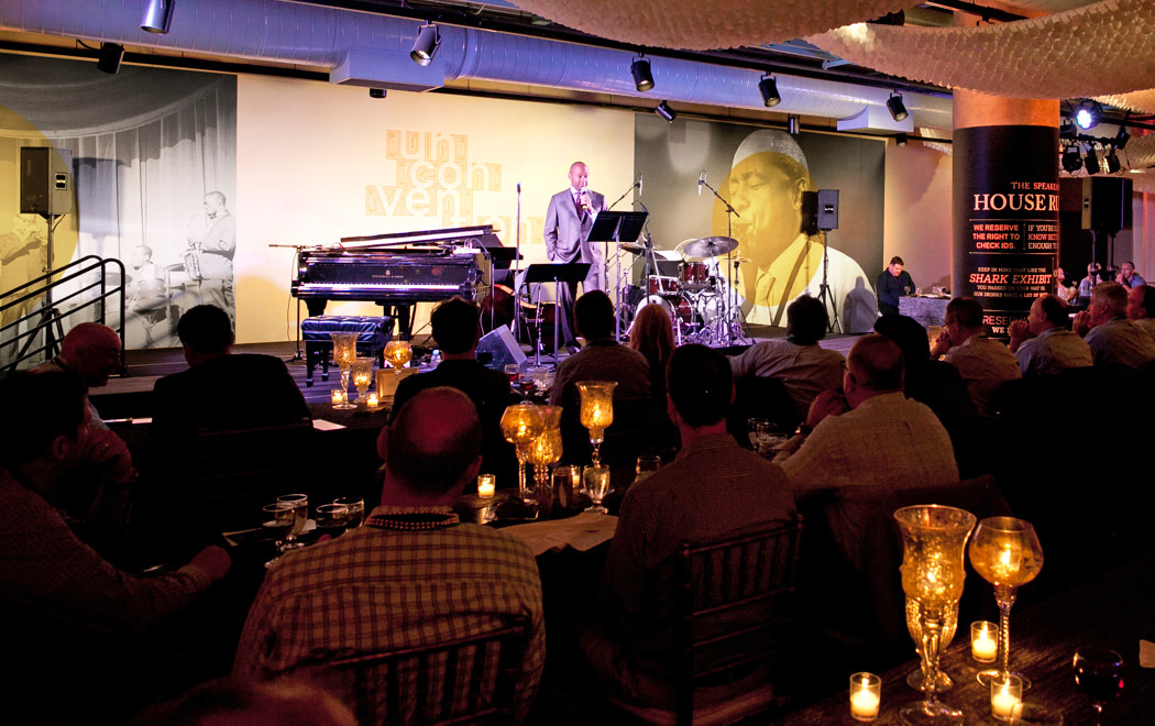 Branford Marsalis on the bandstand at a 2015 KCG Uncon client event reception with a large conference banner behind him.