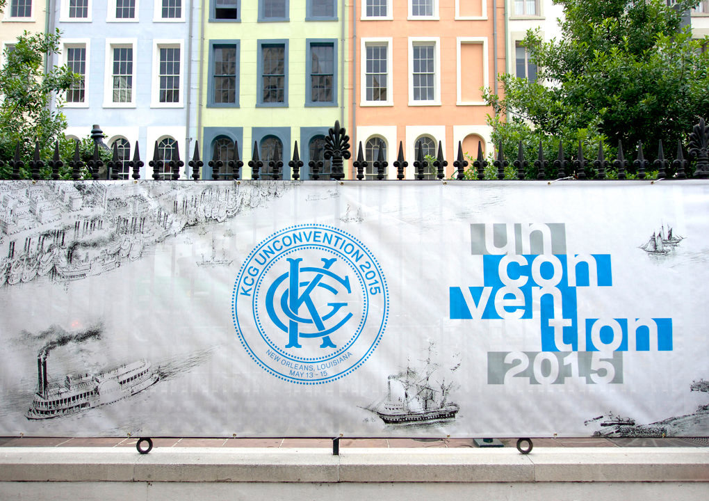 A mural on a fabric banner attached to an ion fence with the 2015 KCG Uncon client event logo and title