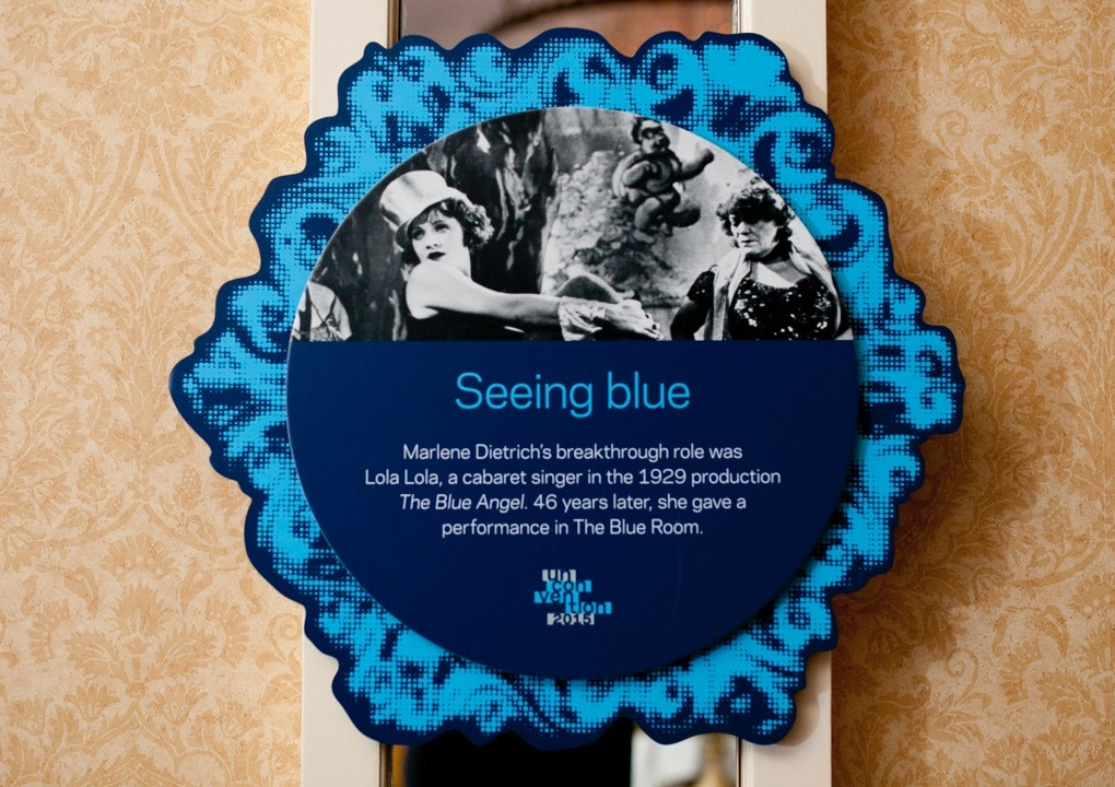 """KCG Uncon event wall hanging with words """"Seeing blue,"""" other text, and a film still picture of the actress Marlene Dietrich."""