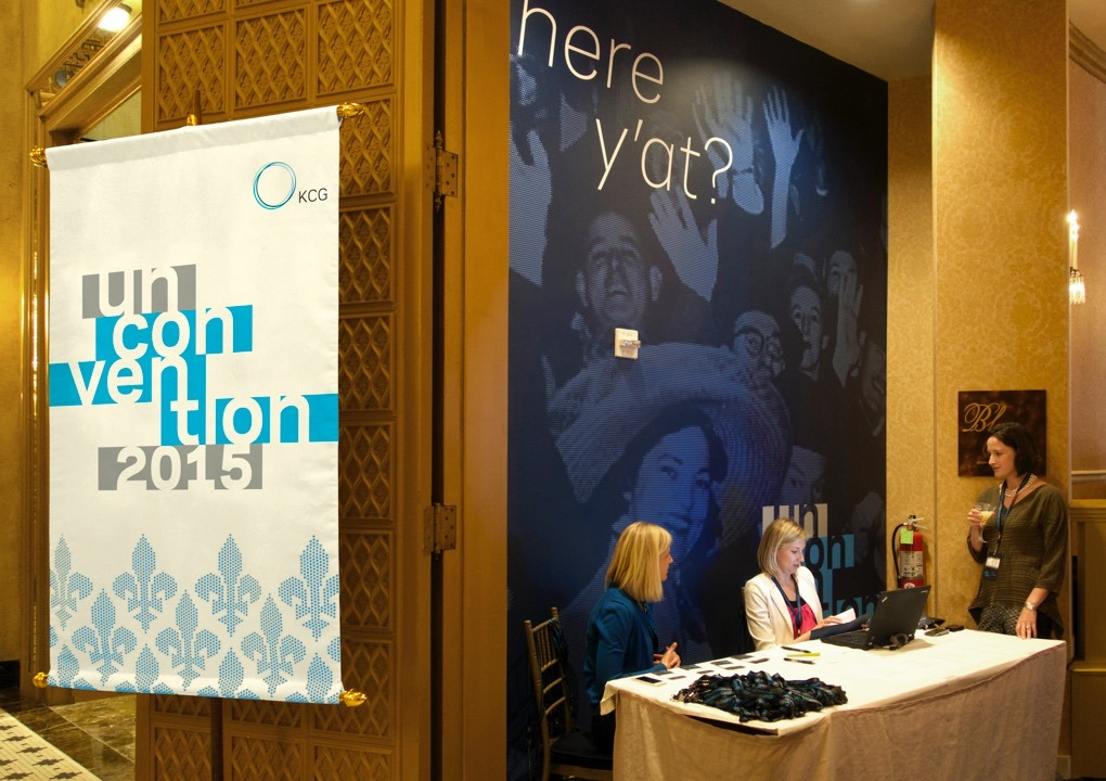 2015 KCG Uncon client event registration table with conference banners on the walls.