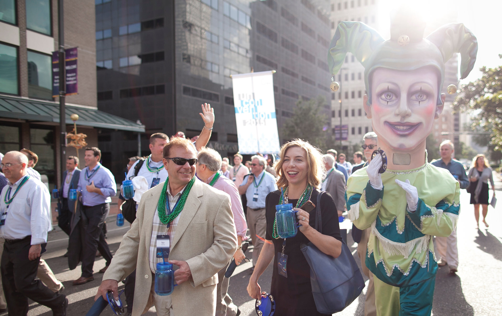 2015 KCG Uncon client event attendees parade on a New Orleans street with a Mardi Gras-style puppet figure.