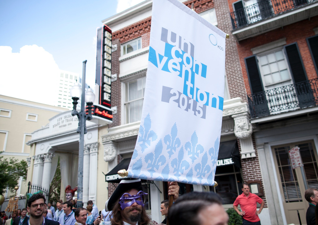 A 2015 KCG Uncon client event banner flies above attendees at a street parade in New Orleans.