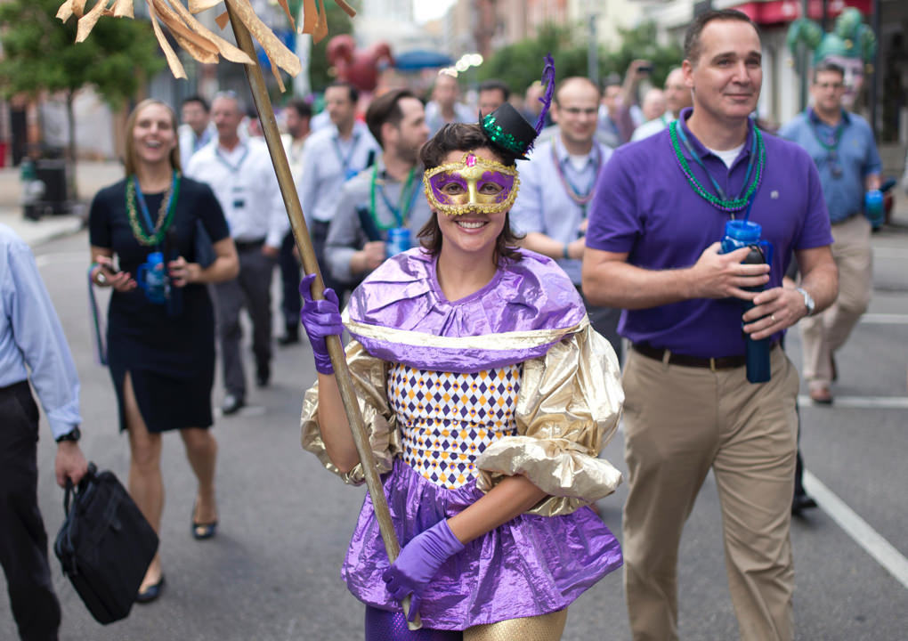 2015 KCG Uncon client event attendees parade on a New Orleans street alongside a figure in a Mardi Gras harlequin costume.