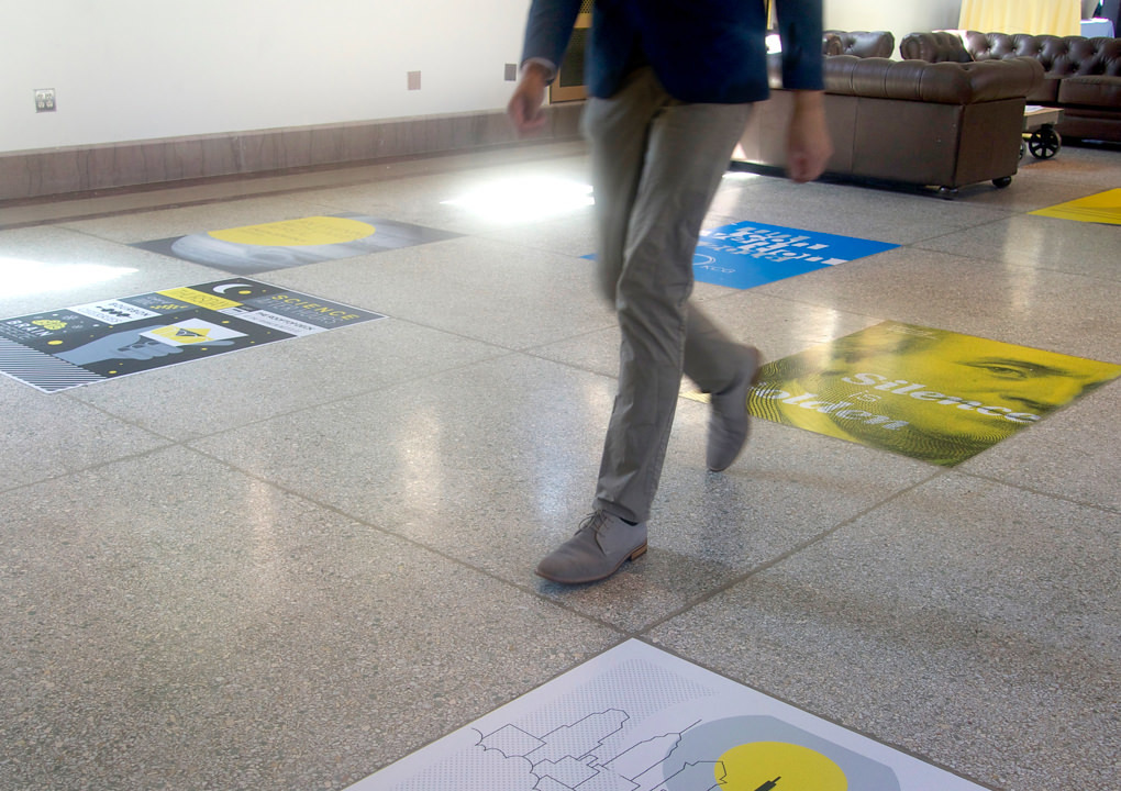 An attendee at the 2016 KCG Uncon client event walking over a terrazzo floor with the large event poster floor stickers.