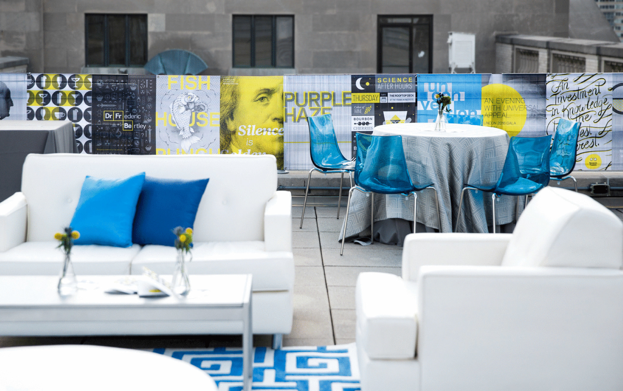 A decorated rooftop reception area at the 2016 KCG Uncon client event rimmed with event posters.