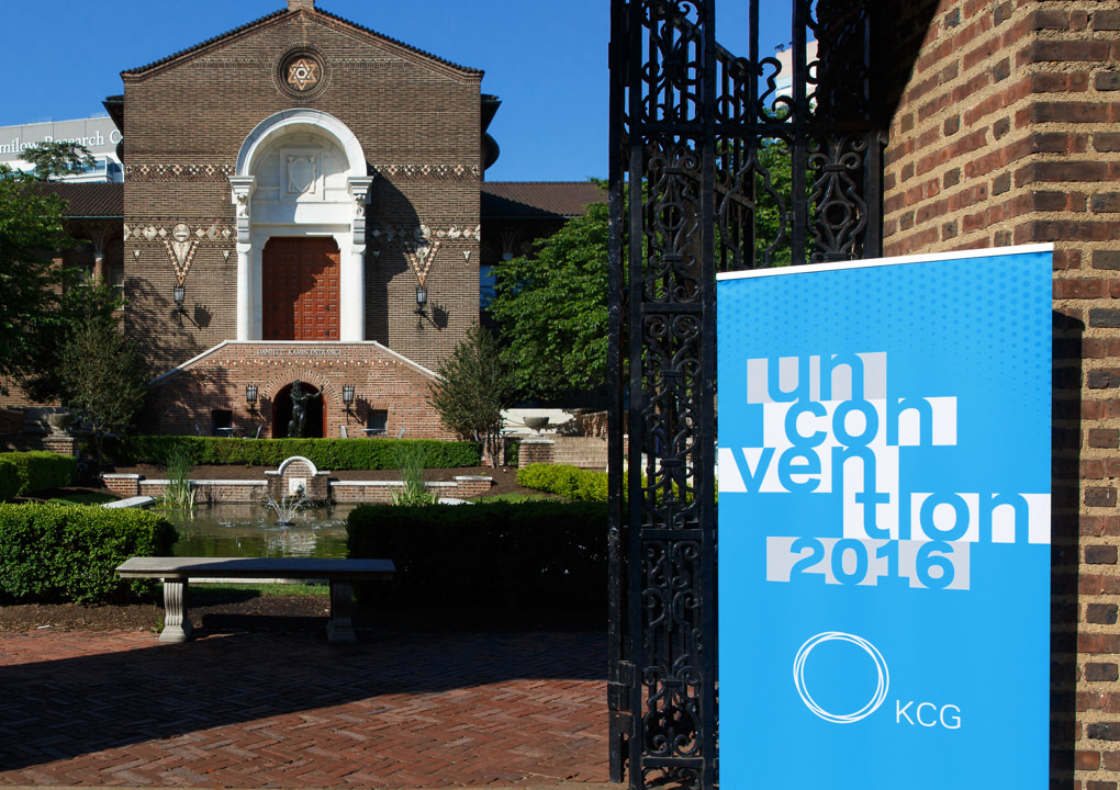 KCG Uncon 2016 client event banner at the entrance gate of a grand building and courtyard.