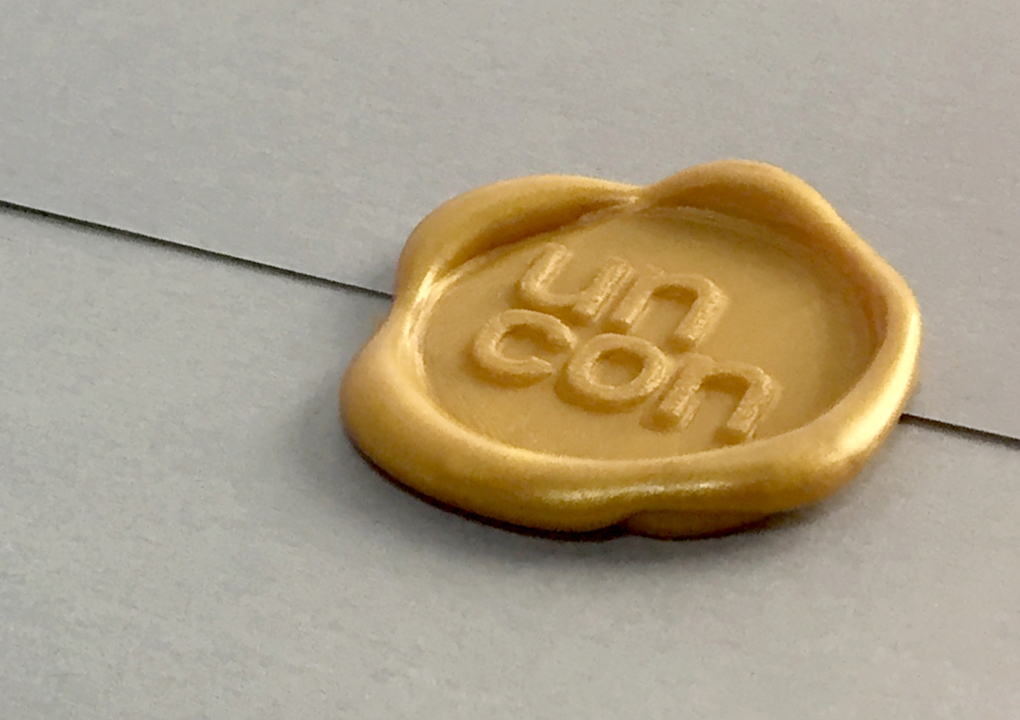 Close up a gold wax seal of the KCG Uncon client event logo on on a grey envelope.