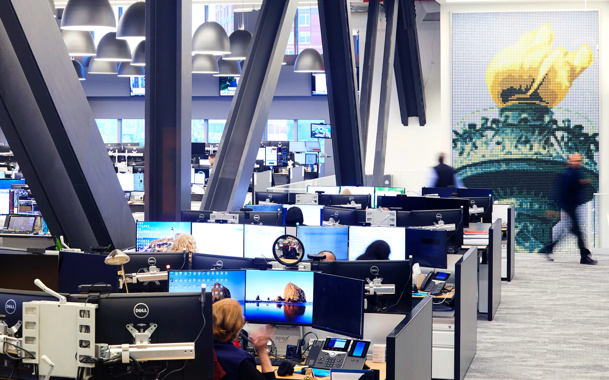 Wide view of computer workstations in KCG's offices. A mural of the torch of the Statue of Liberty is in the background.