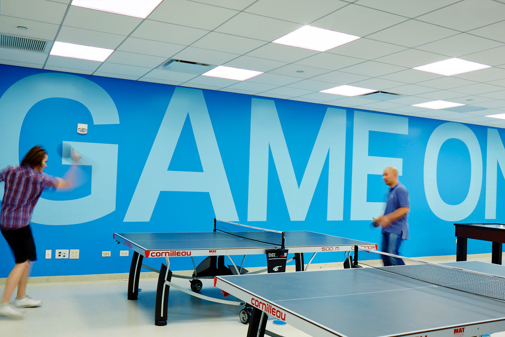"KCG employees play ping pong in front of a blue wall emblazoned with the phrase ""Game on"" in giant letters."
