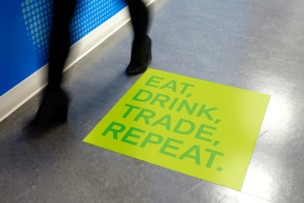 "Blurred legs in motion walk over a floor sticker in the KCG cafeteria printed with the words ""Eat, drink, trade, repeat."""