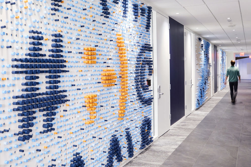 A wall sculpture in the KCG office made of hundreds of colored wooden dowels depicting a hashtag and typographic symbols.