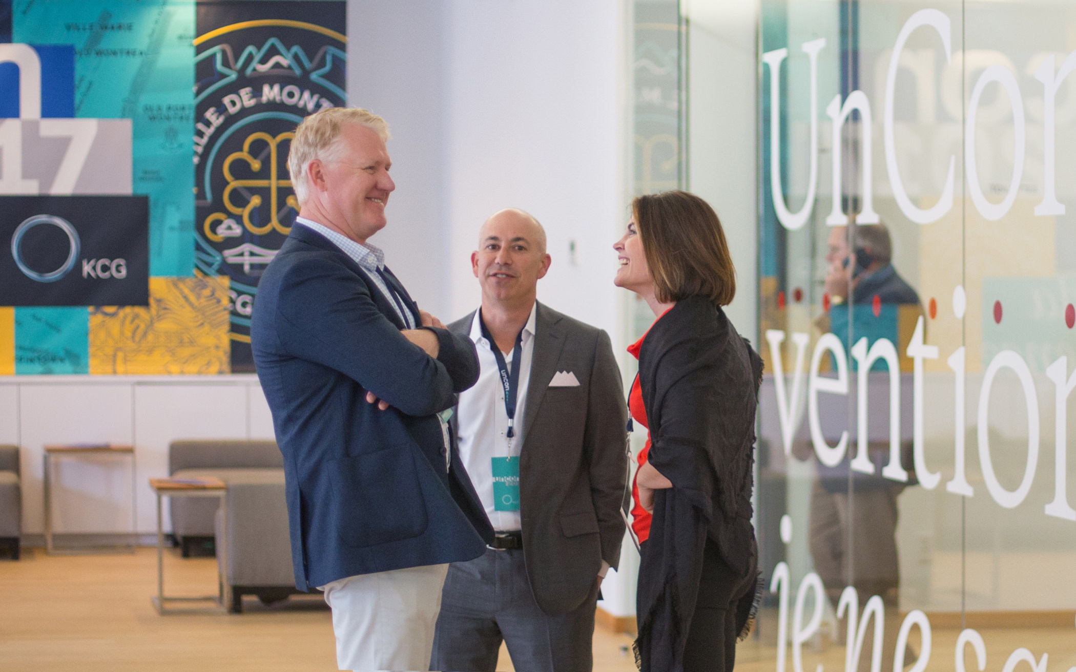 "Three attendees speaking in an open space in front of colorful illustrated signs during the KCG annual ""Uncon"" client event."