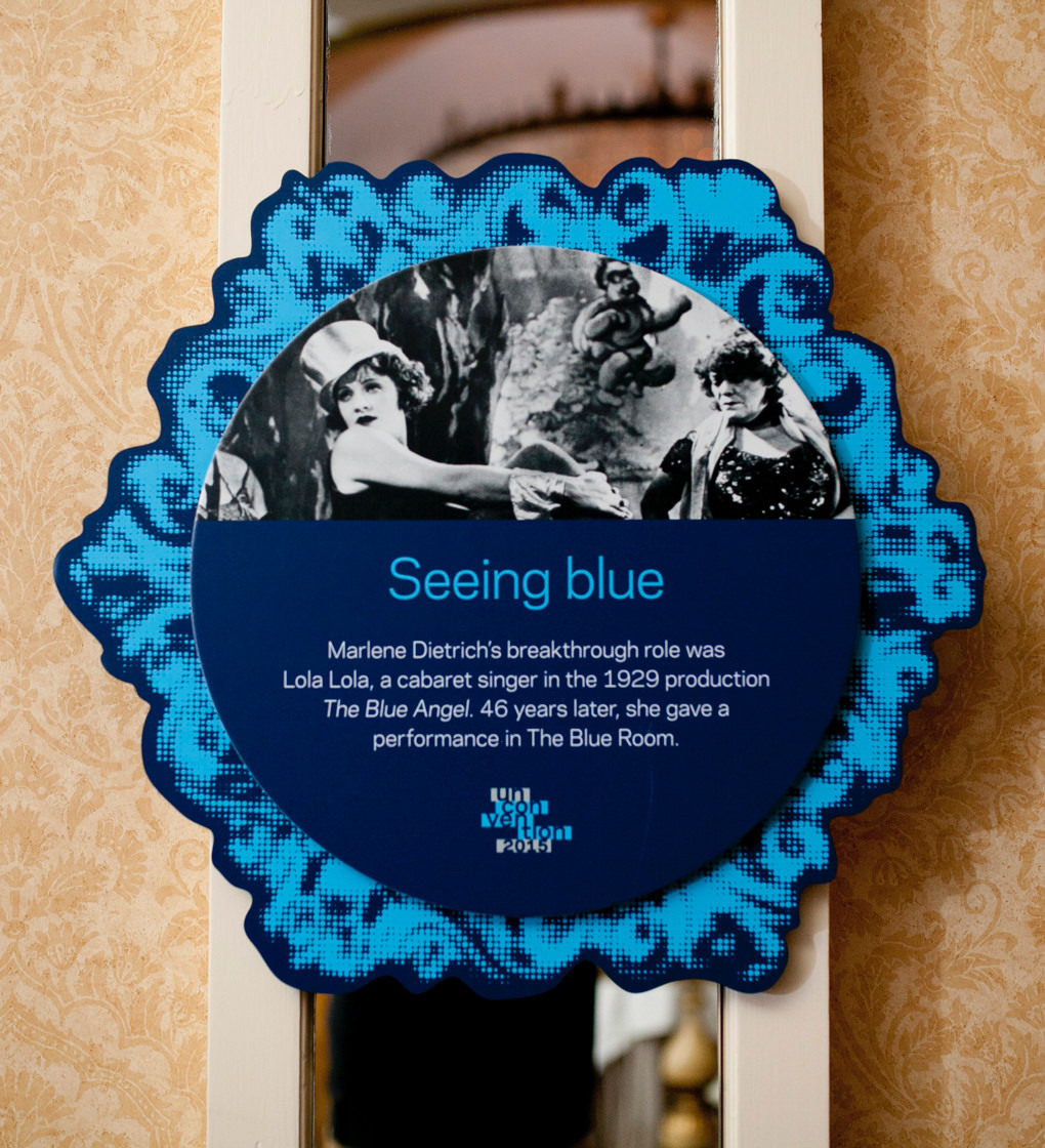 "KCG Uncon event wall hanging with words ""Seeing blue,"" other text, and a film still picture of the actress Marlene Dietrich."
