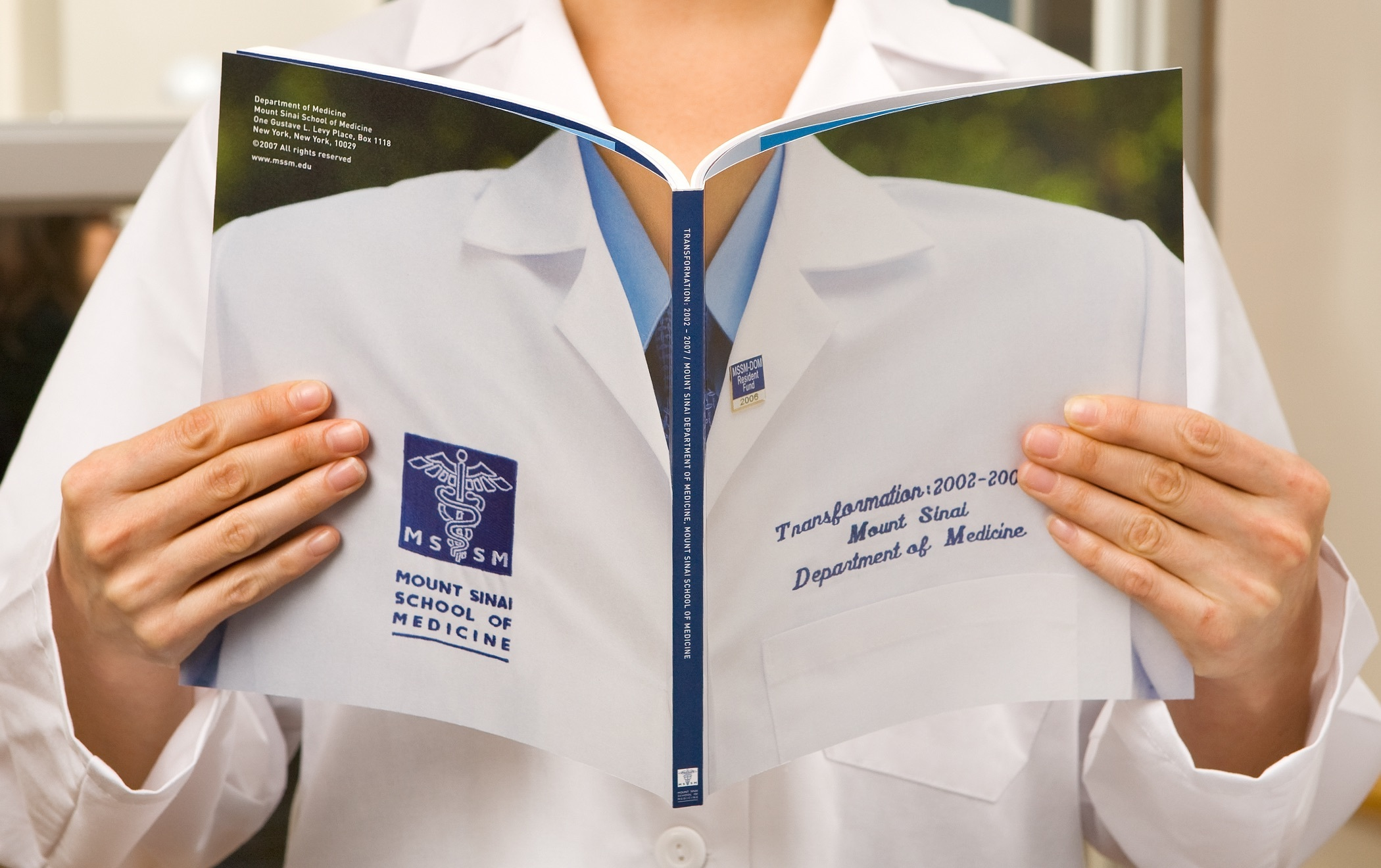 Hands holding open a Mount Sinai School of Medicine yearbook with an image of lab coat spread across the front and back cover.