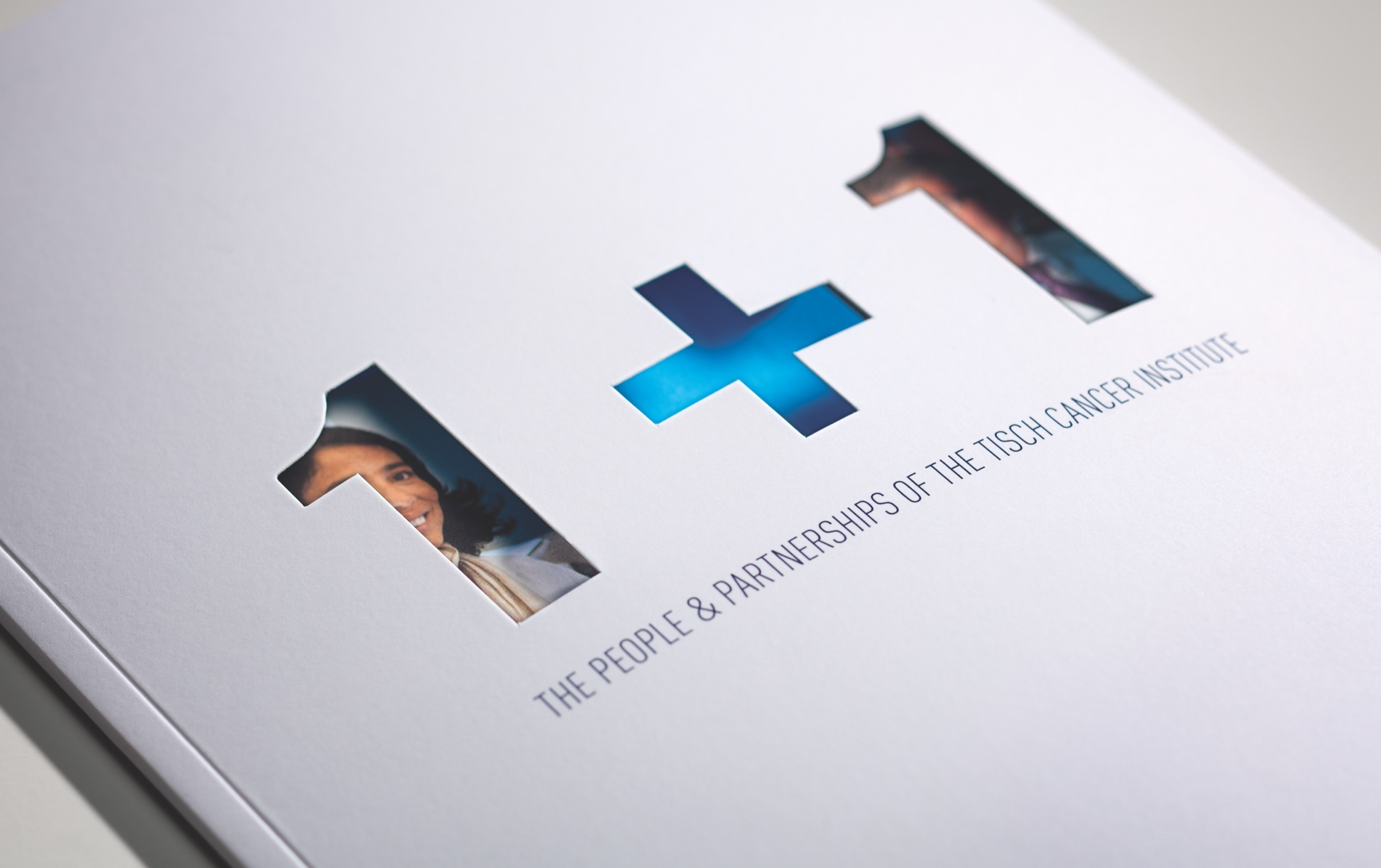 The title text one plus one die cut to reveal a photograph below on the cover of the Tisch Cancer Institute 2011 annual report.