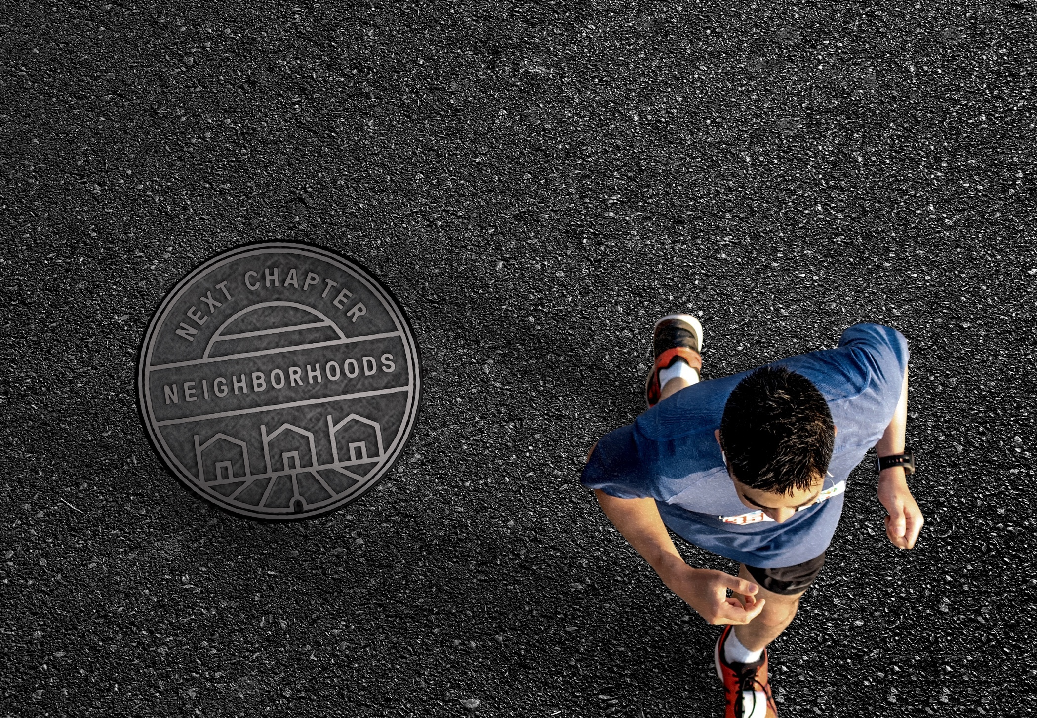 View from above as a jogger runs on a road past a Next Chapter branded manhole cover.