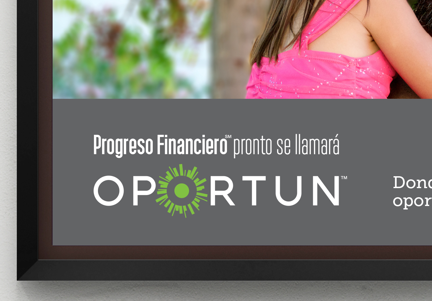 "Cropped view framed wall poster with the Oportun logo and the Spanish phrase, ""Progreso Financiero pronto se llamará."""