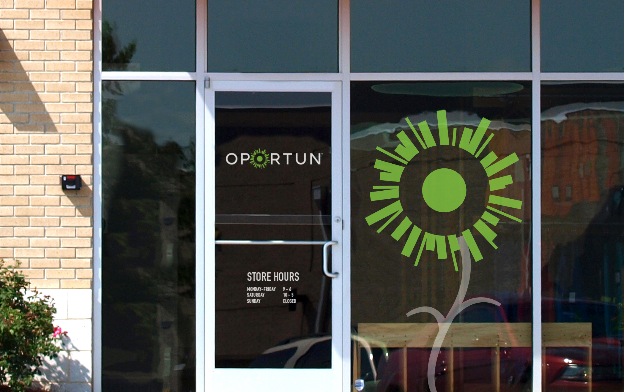 The Oportun logotype and large green-sun symbol on the window of a storefront.