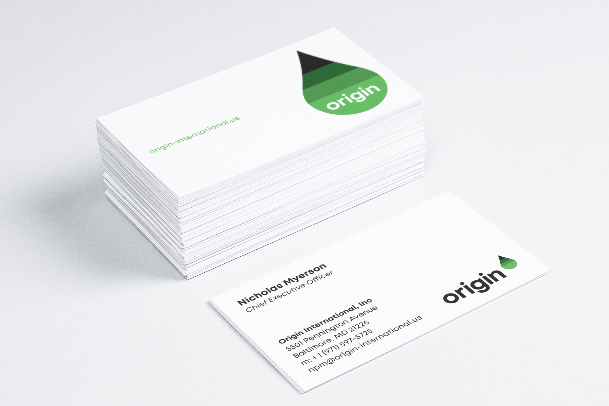 The Origin International logotype and green-gradient droplet symbol painted on white business cards.