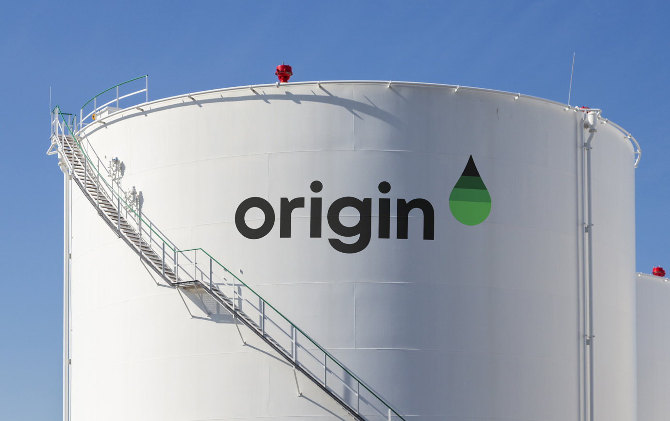 The Origin International logotype and green-gradient droplet symbol painted on a large white holding tank.