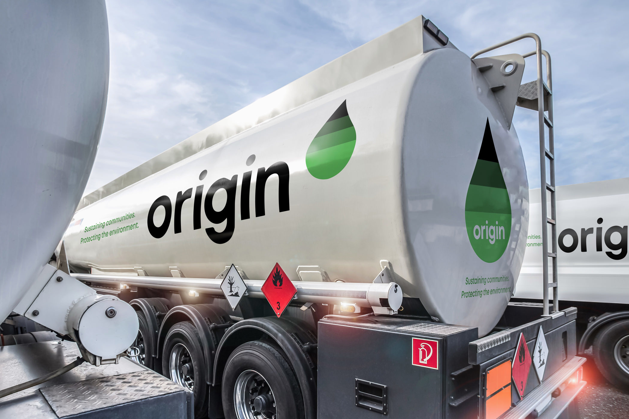 The Origin International logotype and green-gradient droplet symbol painted on a white tanker truck trailer.