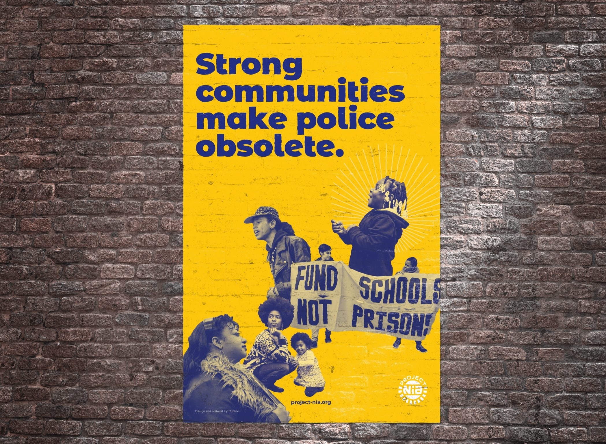 "A Project Nia poster on a brick wall that reads ""Strong communities make the police obsolete"" with images of protesters."