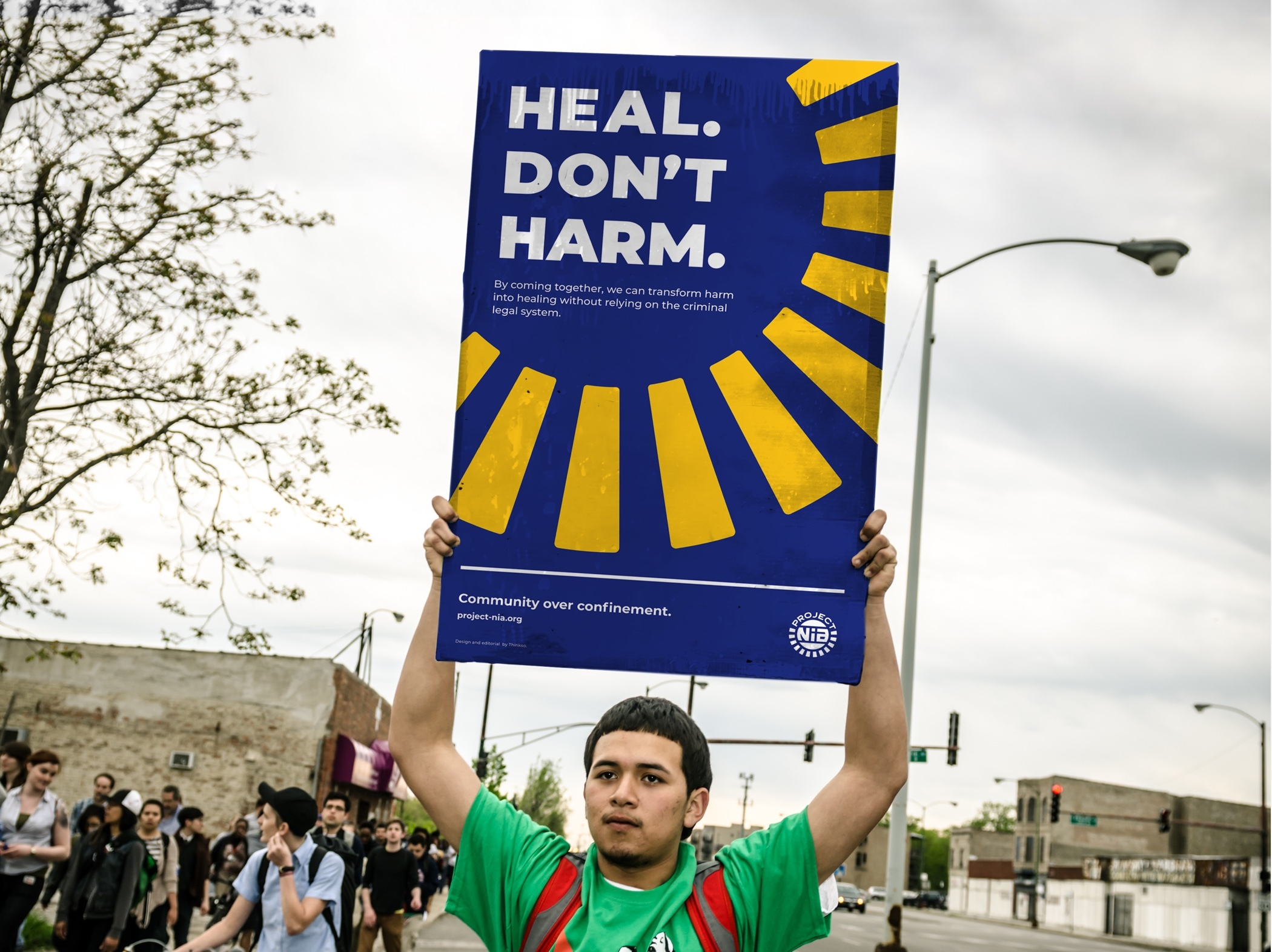 "A young protester in a green shirt holding a Project Nia banner that read ""Heal, don't harm"" overhead."