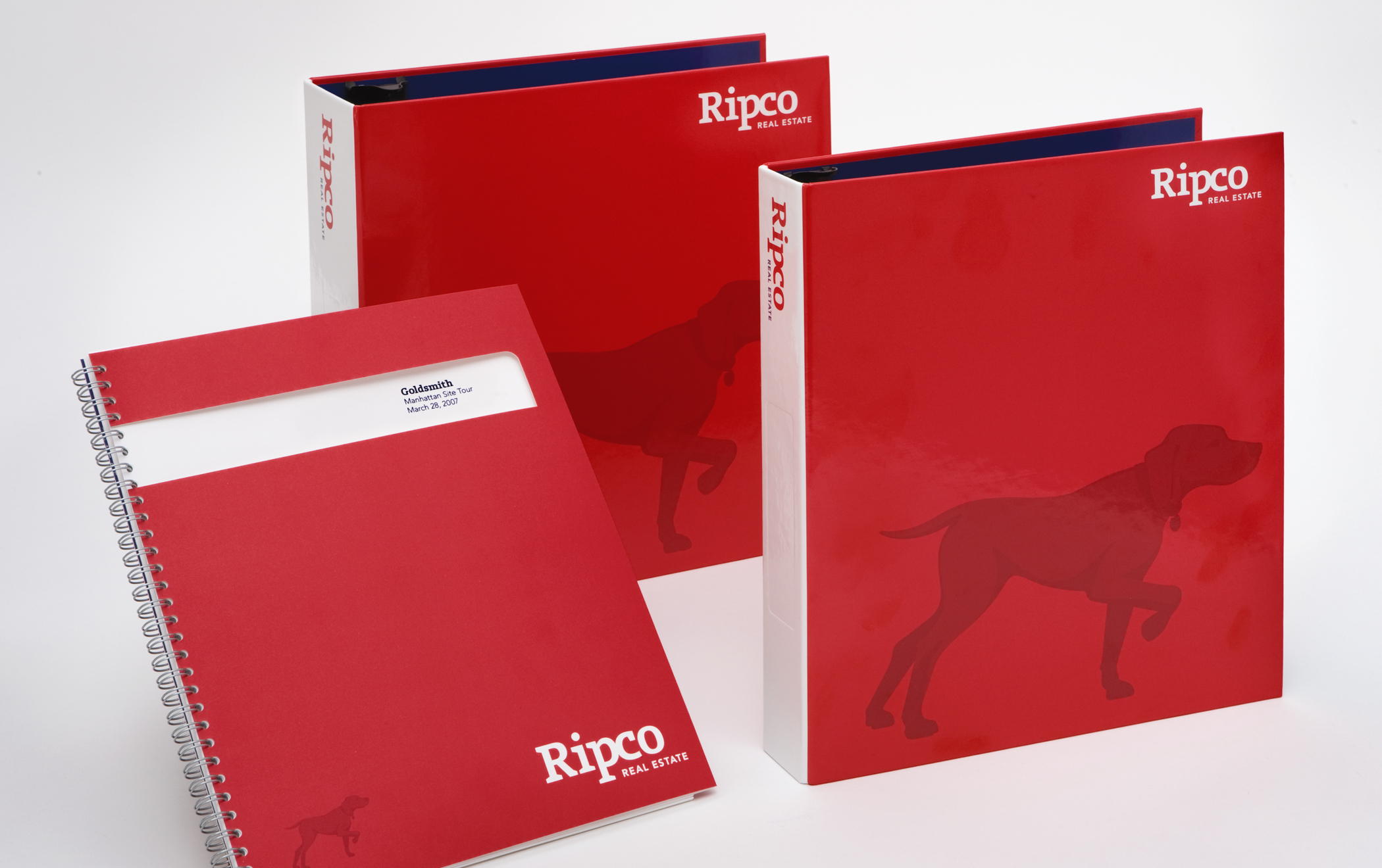 Several red Ripco binders and notebooks featuring the hunting-dog-in-a-pointer-pose brand symbol.